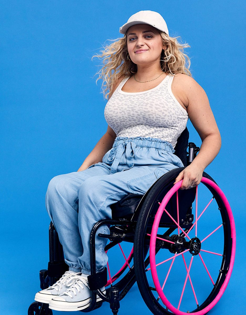 blonde woman using a a black wheelchair with hot pink wheels wearing a white leopard print fitted tank tucked into linen look jogger pants