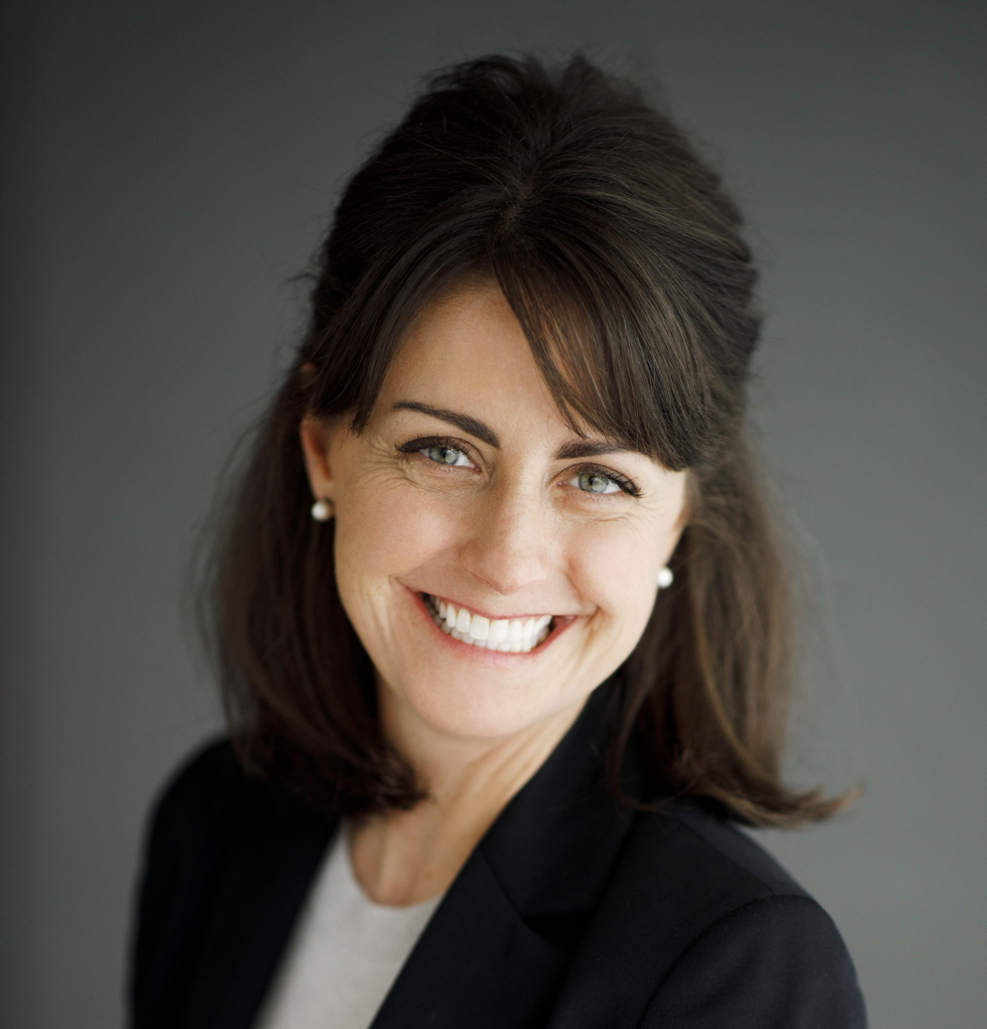 portrait of amy in a black blazer with a grey background