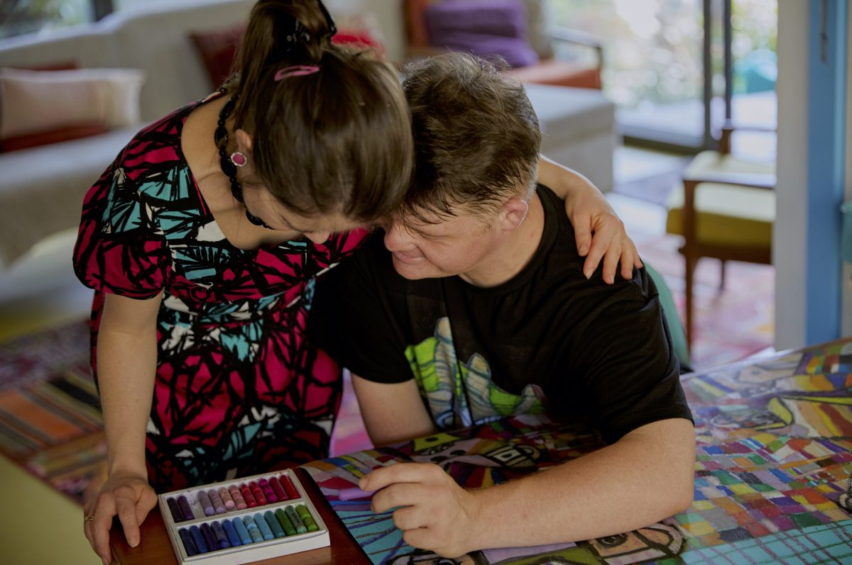 a white woman and white man with down syndrome at a table with their forheads together. She is standing and he is sitting. They have a box of pastel crayons on the table and are drawing