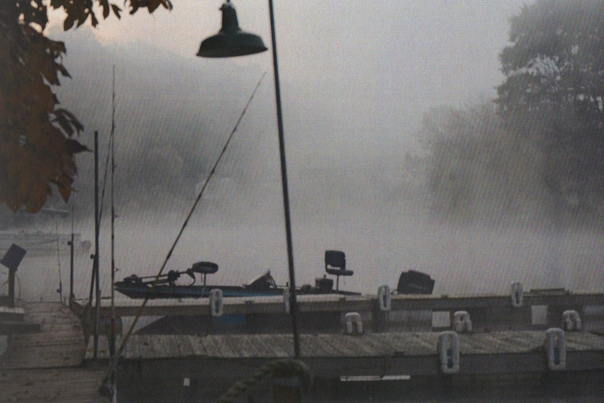 image of bell-shaped lamp post with foggy background with possible trees beyond, dock and pontoon boat in foreground
