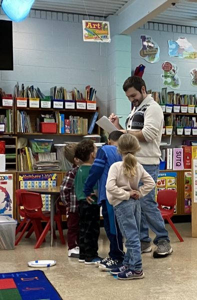 kindergarten classroom with theatre teacher in white sweater with sheets of paper surrounded by four kindergarten children watching him