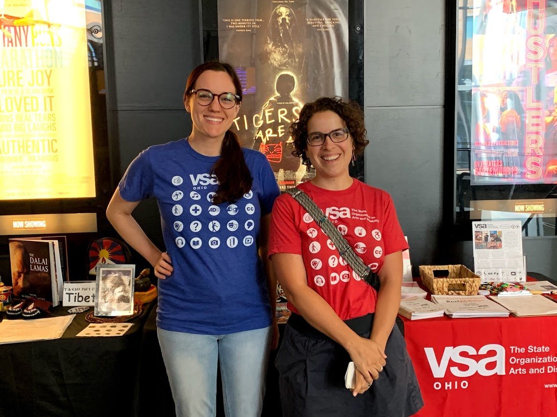 two white women standing in front of movies posters and a table. Both have brown hair. The taller one is wearing a blue VSA Ohio t-shirt and the shorter one is wearing a red VSA Ohio t-shirst and a bag over her shoulder