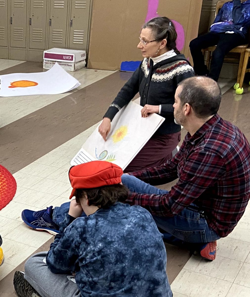 one male student in a red hat and blue tie dyed shirt, one male teacher in a red and blue plaid shirt, and Kris sitting on the floor of a classroom. Kris is wearing a grey sweater and holding a large sheet of paper with a drawing on it.