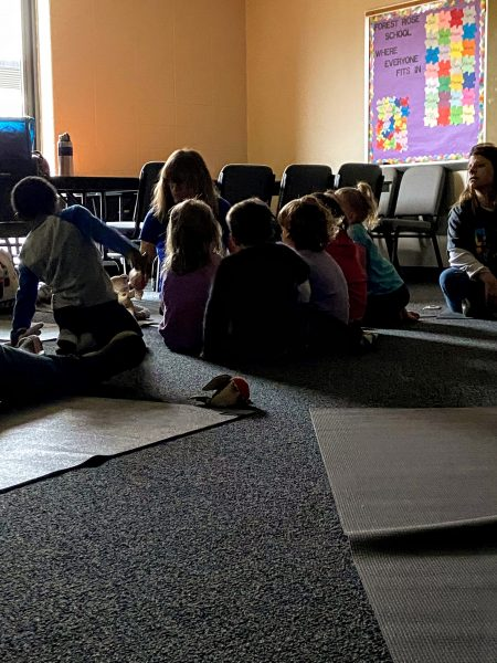 kindergarten students in a dimly lit room sitting together on the floor on yoga mats around their teacher Joanna who is also sitting on the floor on a yoga mat