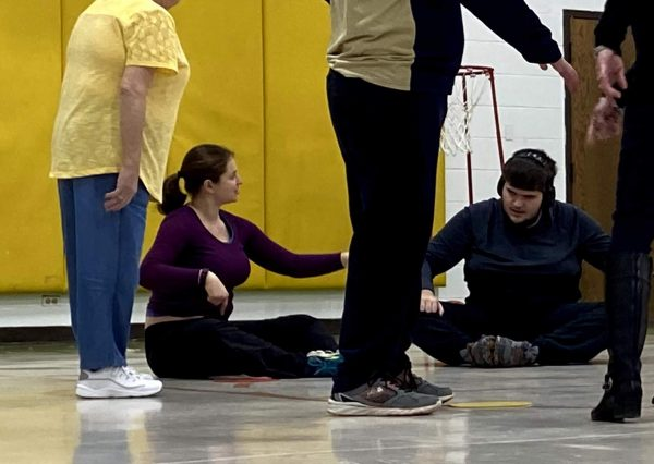 four people in a gymnasium, two sitting on the floor and two standing. Angelica is sitting wearing a maroon top and black pants and she is talking to a man sitting in black pants and a black shirt wearing headphones they are stretching.