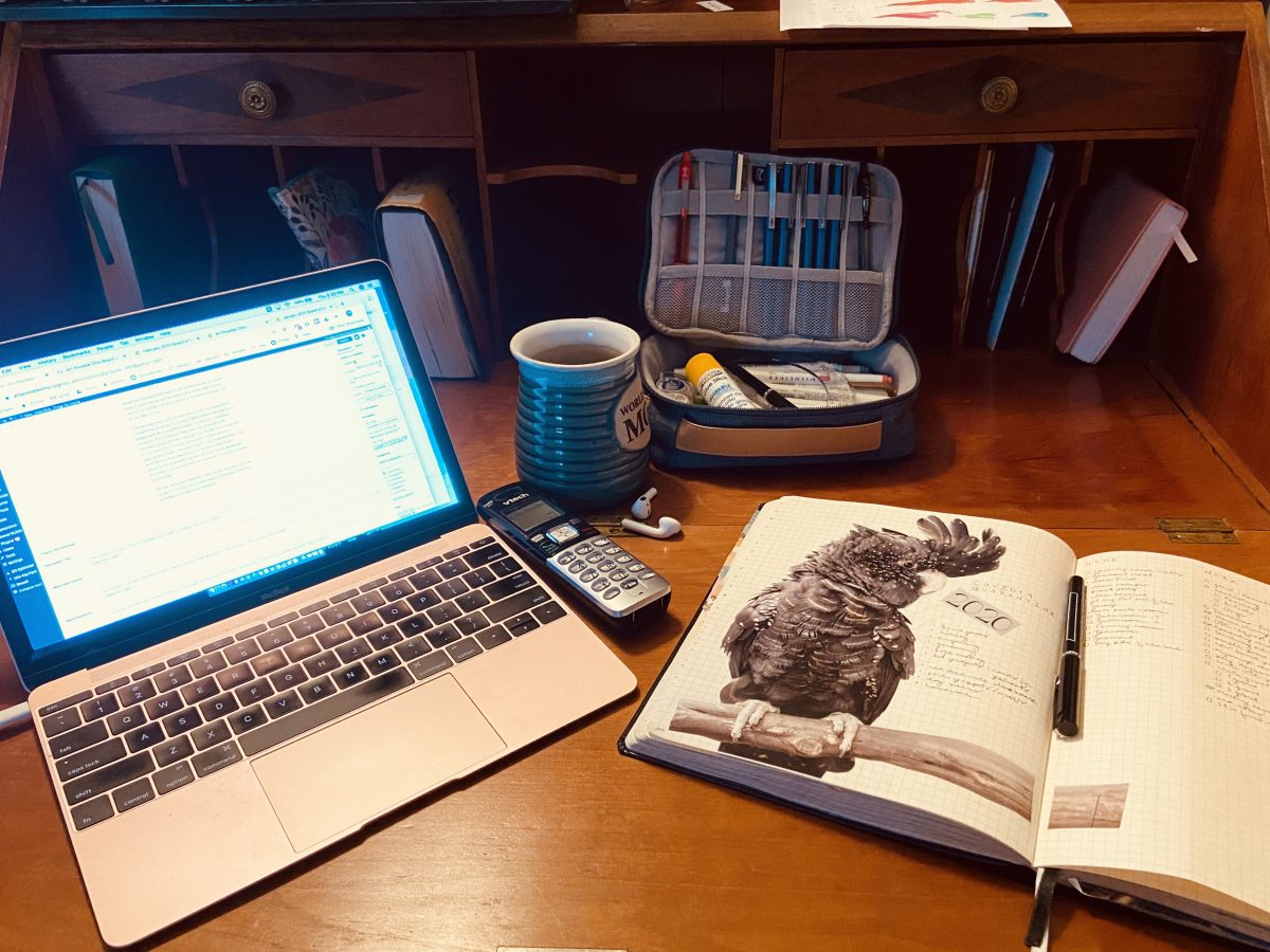 antique desk with laptop, coffee mug, phone, pen case, airpods, and journal with collaged image of a bird
