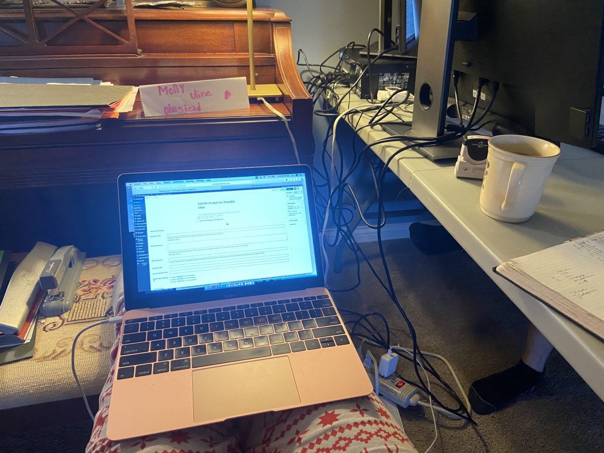 laptop rested on legs with piano and desktop computer monitors in the background.