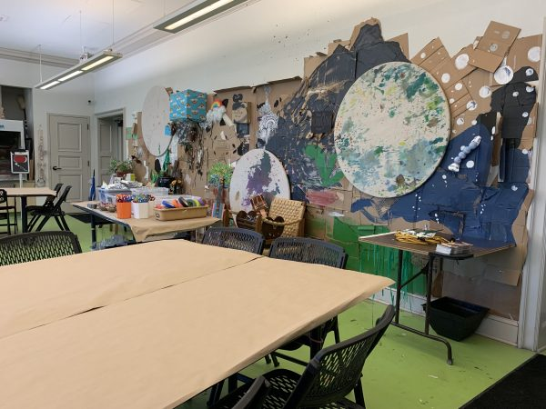 bright studio with green floor and large table in foreground covered in brown kraft paper and wall in background with art installation