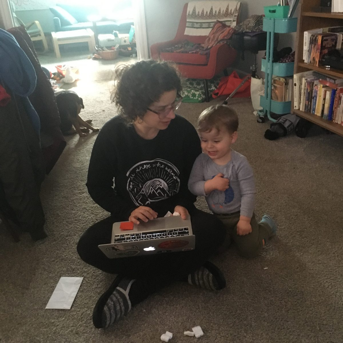 Megan and toddler son sitting on carpeted floor of home with book shelf in the background. Megan is crosslegged with a laptop on her lap.