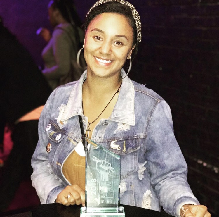 shelby harris, young woman of color in a denim jacket sitting at a table with an award in front of her