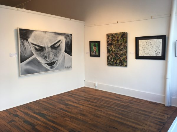 Exhibition image featuring four artworks including a large portrait, and three smaller artworks on white walls