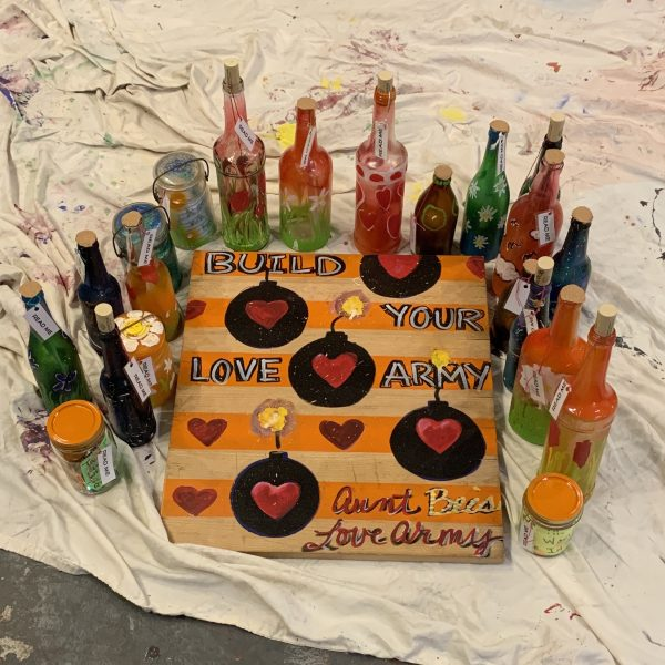 painted bottles placed around a sign that has gold and orange stripes with black bombs that have hearts on them. The sign reads Build your love army, aunt bee's love army