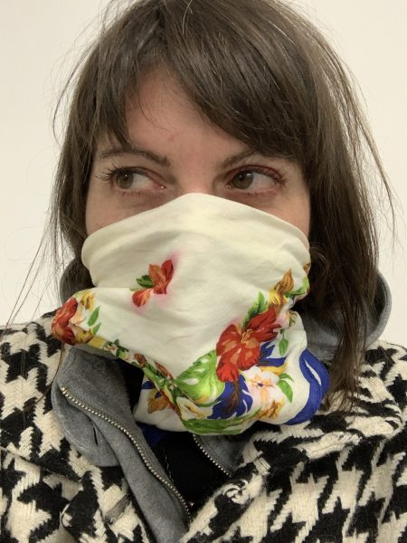 AJ wearing a flowered kerchief over her mouth and nose. She has long light brown hair and is looking to the side.