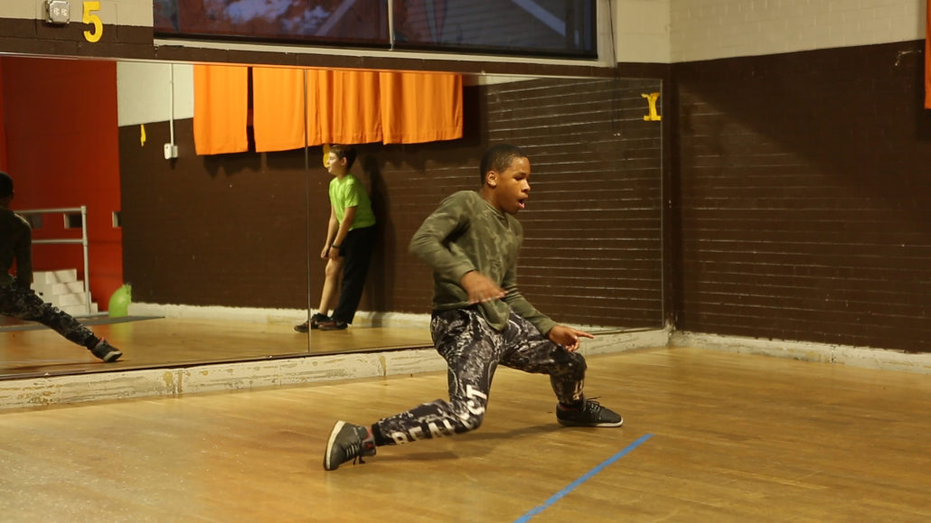 film still of young African American man dancing in a studio with a mirrored wall.