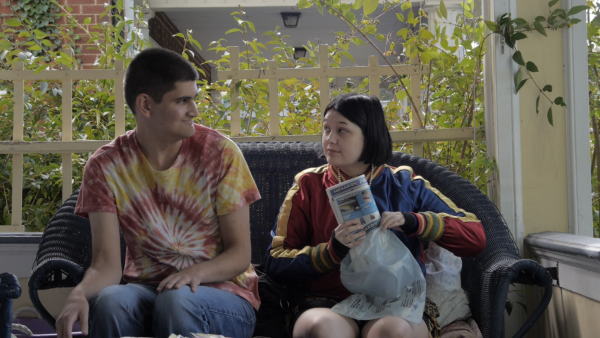 film still from those who spring from me showing two characters sitting on a couch on a porch with a trellis in the background. The male character is white and young, he is wearing a pink and yellow tie dye shirt and jeans. he is looking at the female character who is also white and young and wearing a maroon jacket and holding a newspaper