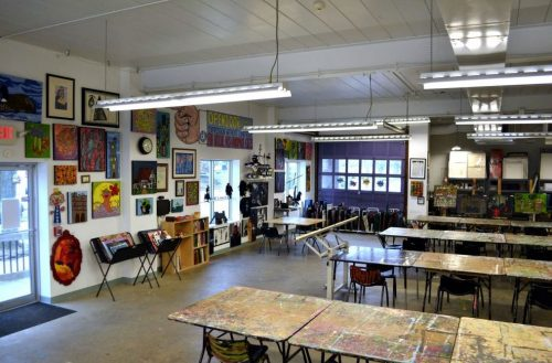 large, open, bright, art studio with long tables in foreground and art on the walls in the background with art storage racks beneath