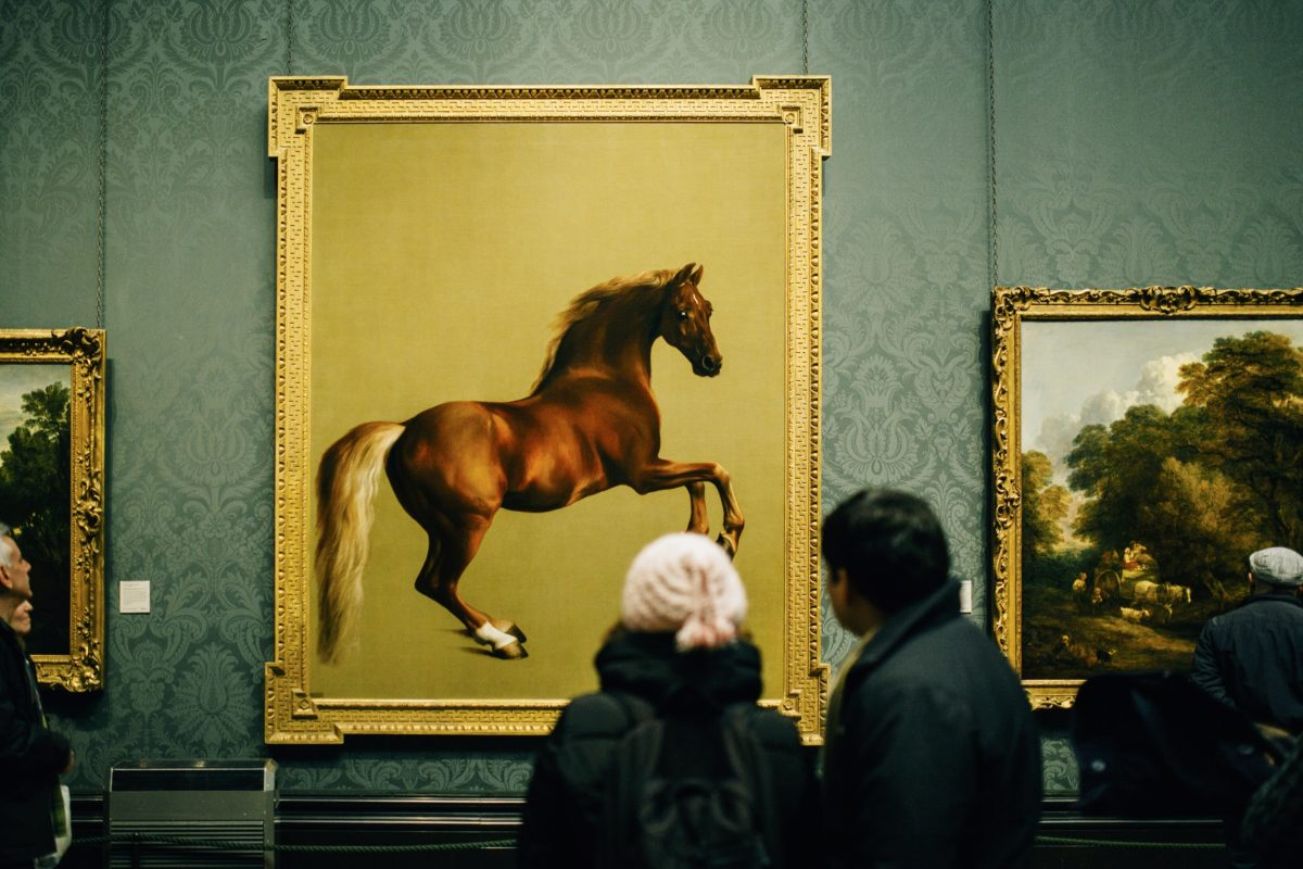 two people facing away from the camera looking at a painting of a horse on a gold background in a gold fram on a green gallery wall in a museum