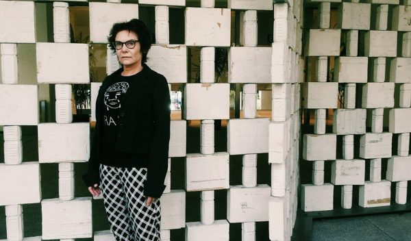 white woman wearing black and white checkered pants and a black top standing in front of a white graphic wall