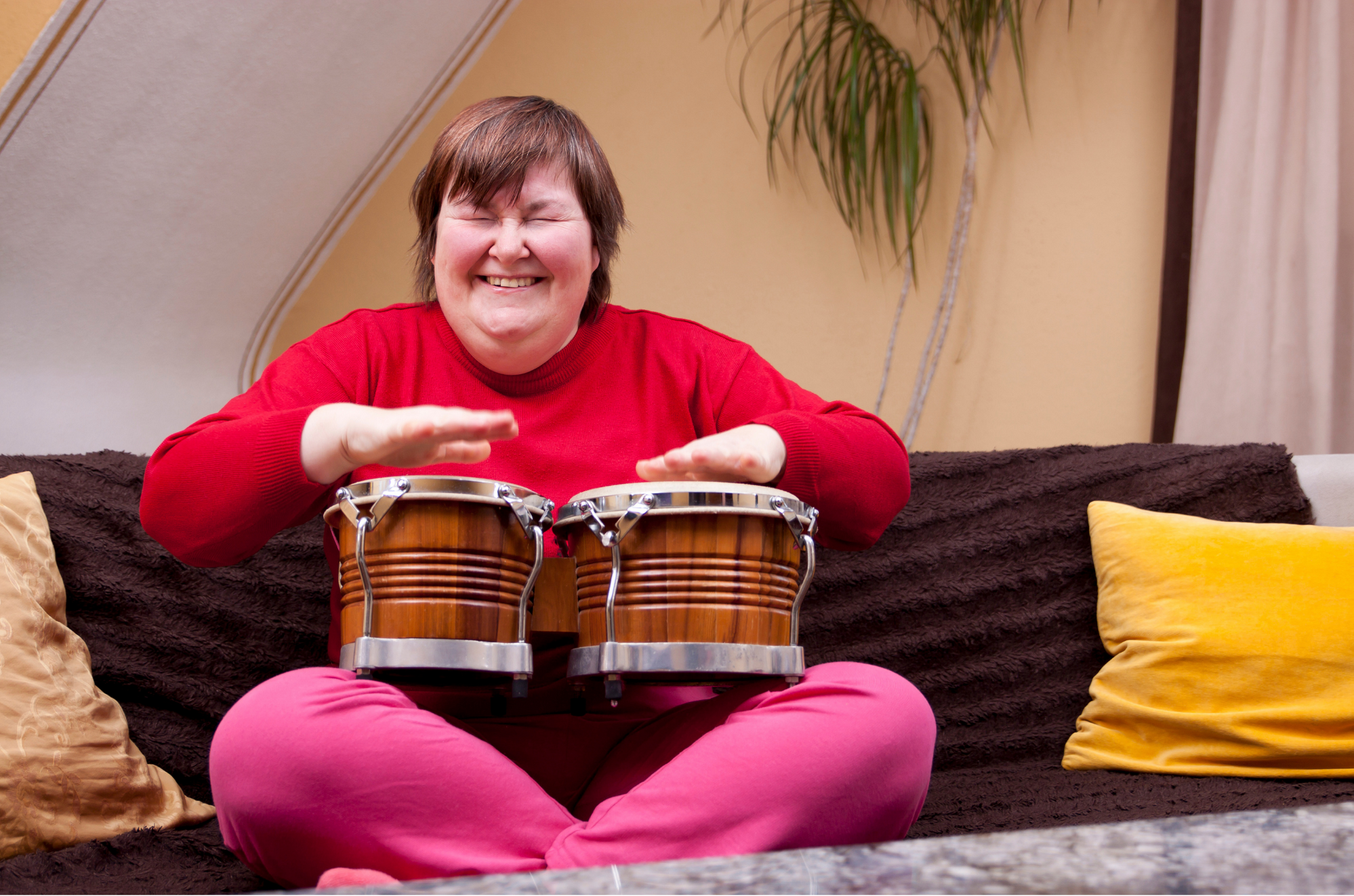 woman with disability wearing red shirt and hot pink pants sitting cross-legged on a modern sofa playing bongos balanced on her knees