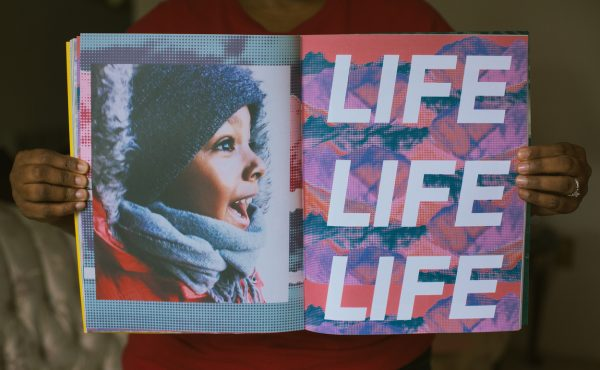 zine held open by african american hands to left hand page page showing profile image of smiling african american boy in knit cap and hooded parka and right hand page showing stylized red and violet background with LIFE LIFE LIFE printed over in block italicized letters.