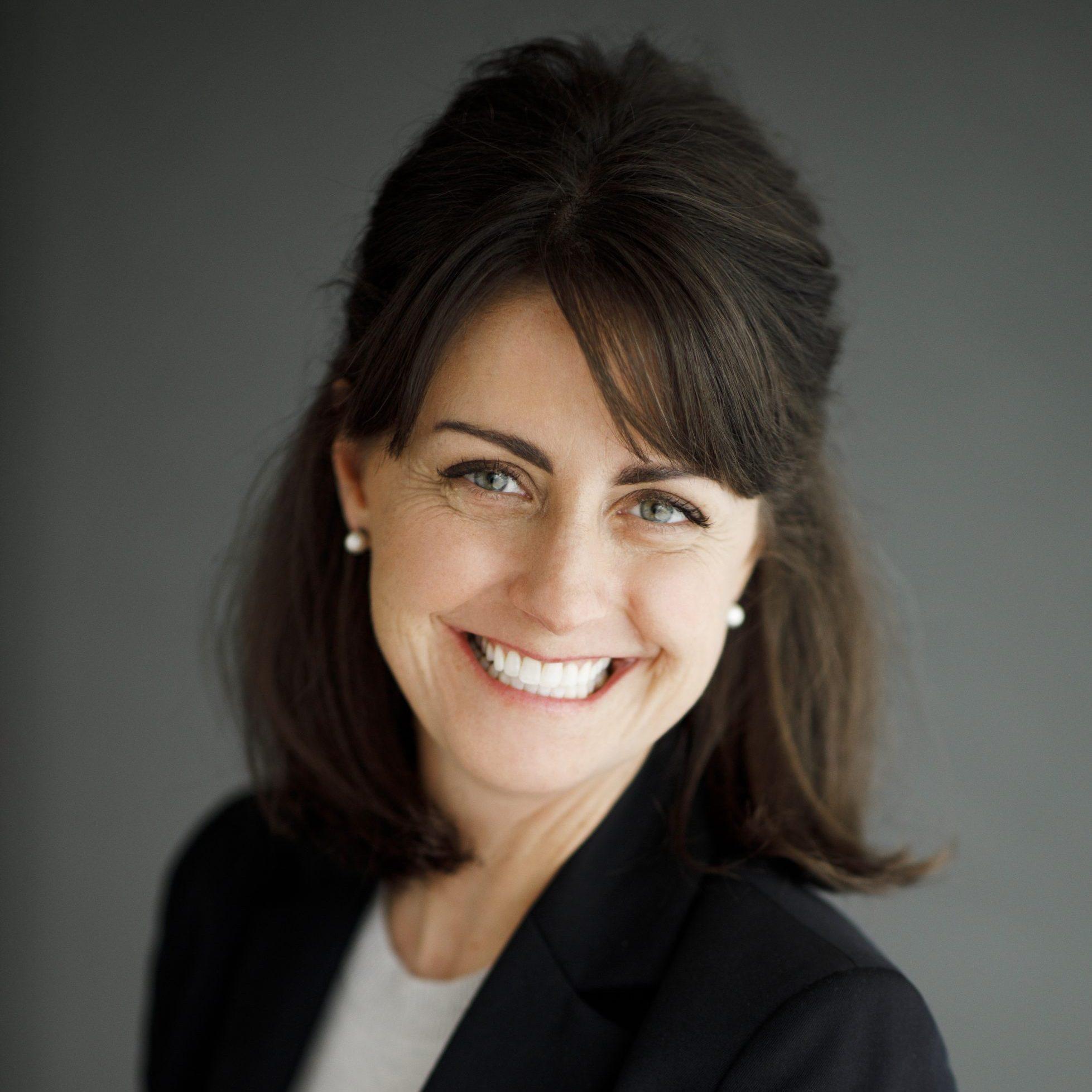 portrait of amy in a black blazer with a grey background