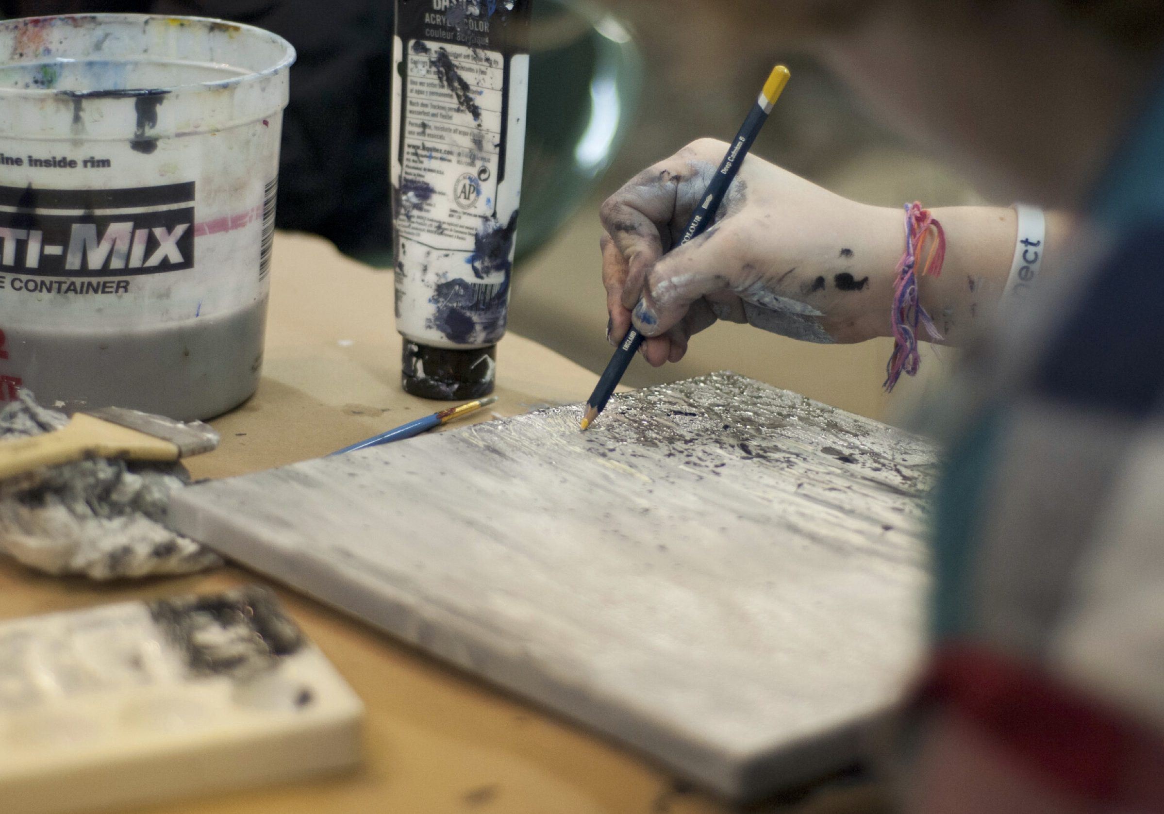 person working on a painting with art supplies around it, only their hand working is visable