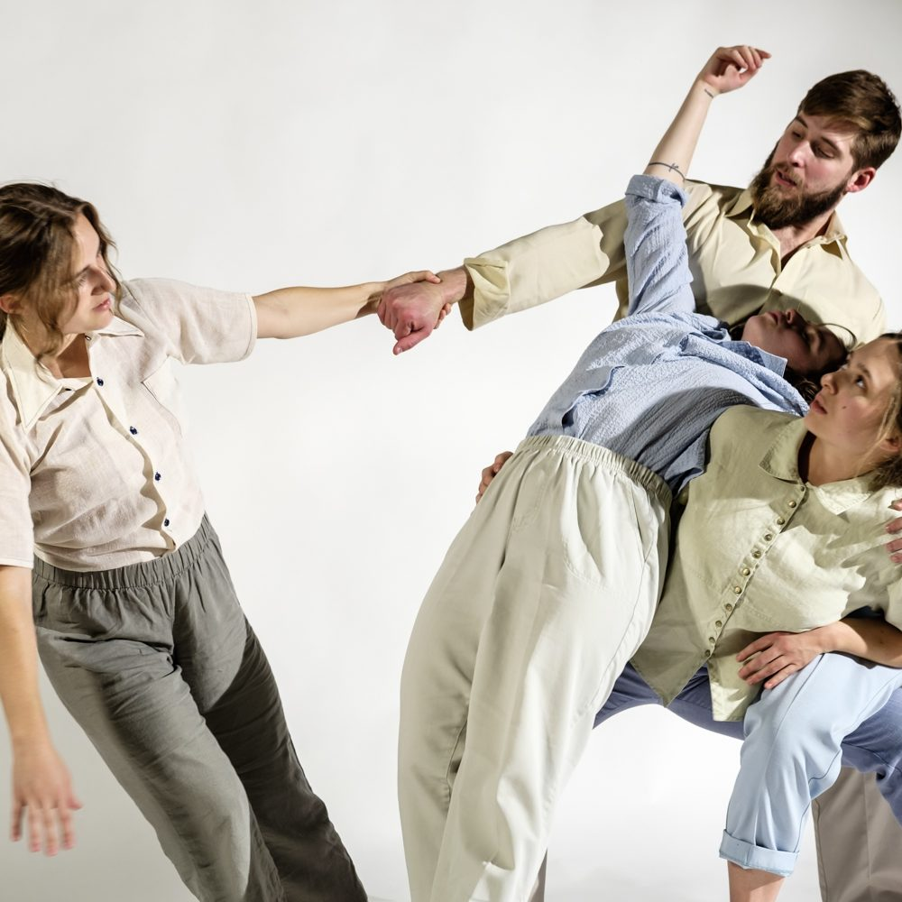 five dancers in light colored loose clothes. Four dancers are leaning on each other with the fifth dancer reaching across to them.