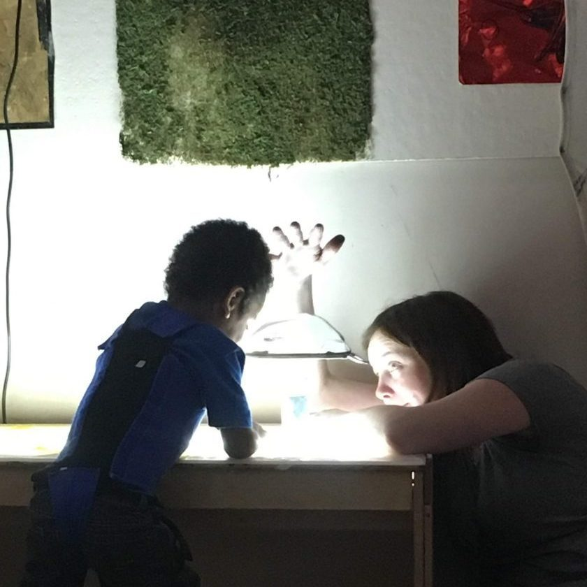 boy in blue shirt facing away from camera and playing on light table with teacher sitting next to light table on floor helping him play