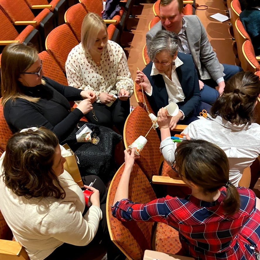 group of museum professionals sitting in an auditorium inventing a device to aid communication using art supplies