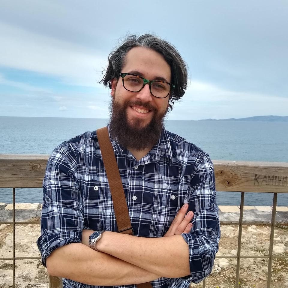 white man with dark hair, beard, and glasses wearing a blue plaid shirt and brown messenger bag standing with arms crossed and smiling in front of a fence with a large body of water in the background
