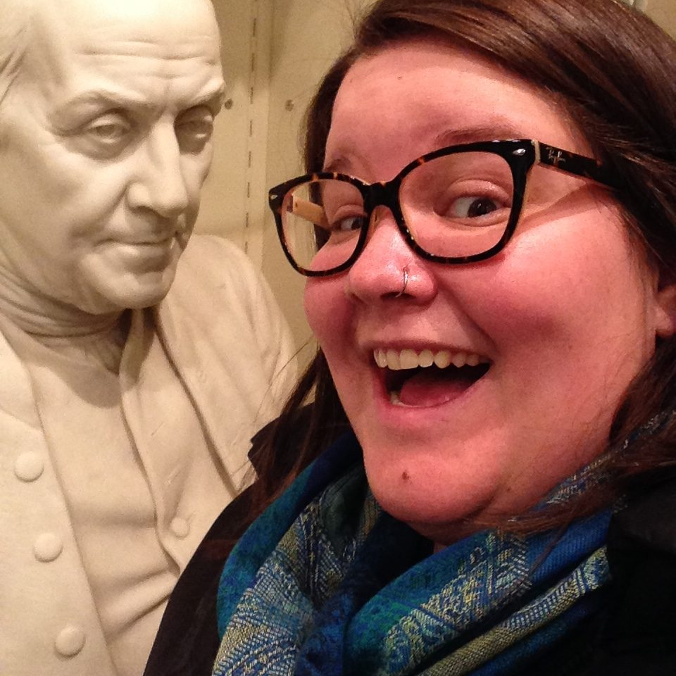close-up photo of Mary in a blue scarf and black top wmiling with black rimmed glasses in front of a marble bust of a man