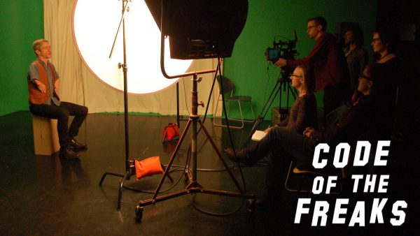 film still from code of the freaks showing an actor sitting on a soundstage to the left with the film crew to the right of the image