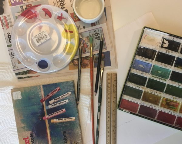 flatly image of art supplies - Large sheet of drawing paper, pencil with eraser, watercolor pans, paint brush, oil pastels, container of water, newspaper, paper towels, ruler
