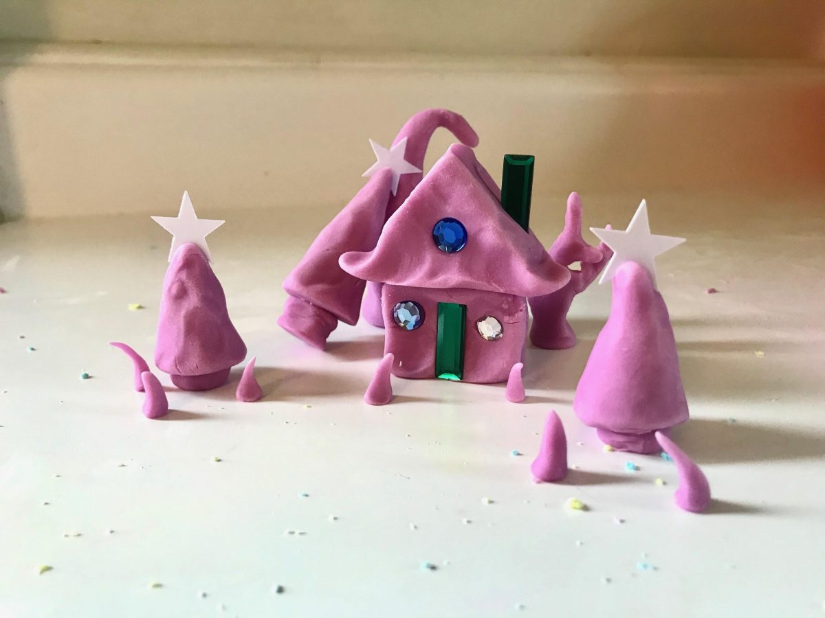 small trees, cabin, and creatures made with purple-pink clay and embellished with green and white plastic gem details.