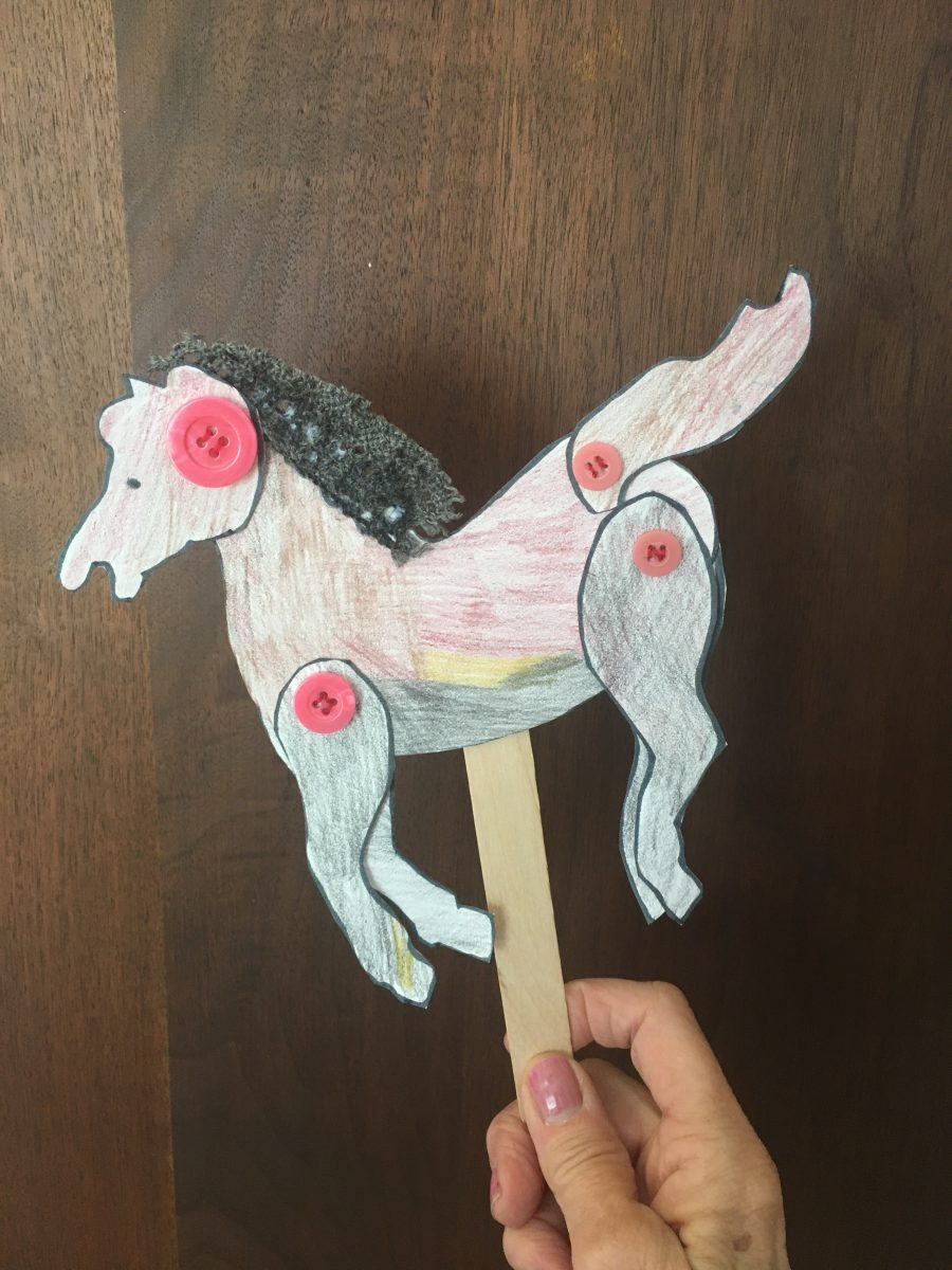 paper horse with moving joints attached by pink buttons on a popsicle stick