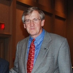 candid portrait of white man in grey suit, blue shirt, and red tie.