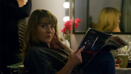 light skinned woman with long blonde hair and bangs sitting in a dressing room with an open magazine looking away from the magazine to the left of the screen